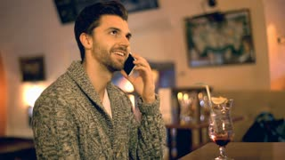 Handsome man chatting on cellphone and drinking alcoholic beverage