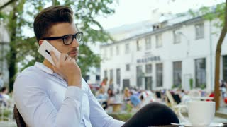 Handsome man having a conversation on cellphone and drinking coffee