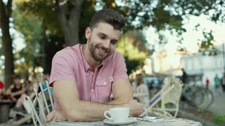 Handsome man talking with someone in the outdoor cafe and smiling