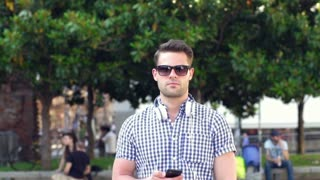 Handsome man walking on the square and chatting on cellphone, steadycam shot
