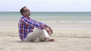 Handsome young man relaxing on the beach, slow motion shot at 240fps