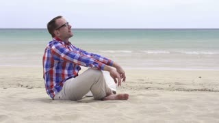Handsome young man relaxing on the beach, slow motion shot at 60fps