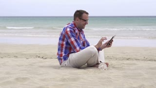 Handsome young man with tablet relaxing on the beach