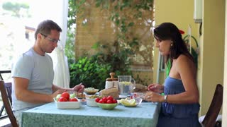 Happy, attractive couple eating breakfast together on the terrace, steadycam