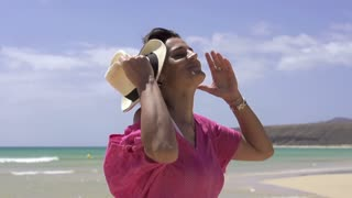Happy beautiful woman standing on the beach, slow motion shot at 240fps