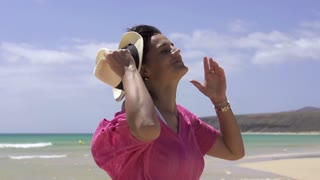 Happy beautiful woman standing on the beach, slow motion shot at 60fps