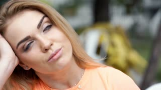 Happy, blonde girl relaxing outdoors and thinking about something, steadycam sho