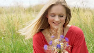 Happy, blonde girl sitting in the grain and holding field flowers