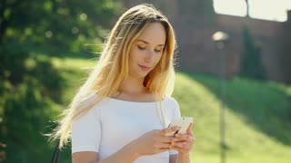 Happy, blonde girl standing outdoors and texting messages on smartphone