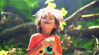 Happy boy eating sandwich in forest, steadycam shot, slow motion shot at 240fps