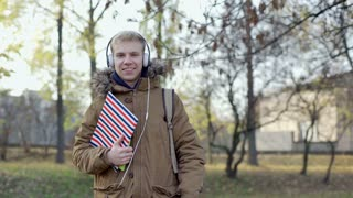 Happy boy listening music on headphones and smiling to the camera