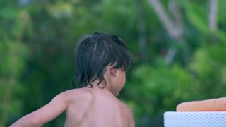 Happy boy playing in the pool, slow motion shot at 240fps