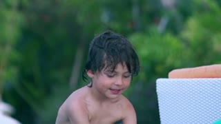 Happy boy playing in the swimming pool, slow motion shot at 240fps