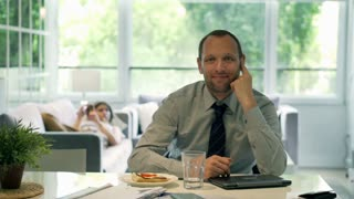 Happy businessman sitting at home and smiling to the camera