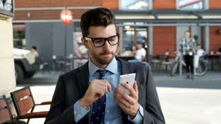 Happy businessman sitting outdoors and browsing internet on smartphone, steadyca