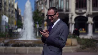happy businessman using his cellphone and standing by the fountain, slow motion