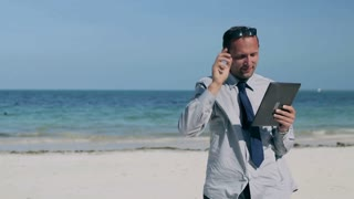 Happy businessman working on tablet on the beach