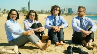 Happy businesspeople sitting on the beach and showing thumbs up to the camera, s
