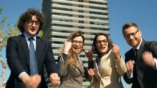 Happy businesspeople standing outdoors and smiling to the camera, steadycam shot
