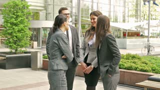 Happy businesspeople standing outside and chatting