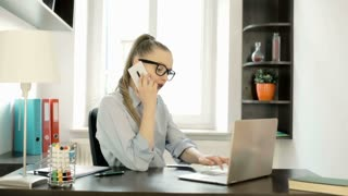 Happy businesswoman chatting on cellphone in the office and working on laptop, s