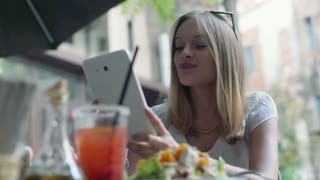 Happy businesswoman having a break in the outdoor cafe and browsing internet on