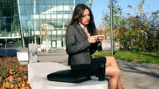 Happy businesswoman sitting outside the building and texting on cellphone