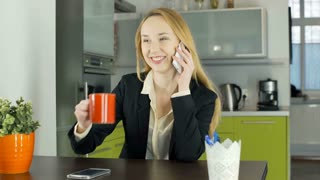 Happy businesswoman talking on cellphone and drinking coffee during break, stead