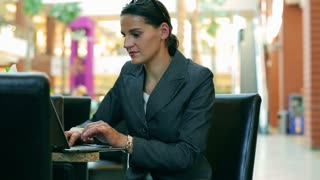 Happy businesswoman working on laptop in the resturant in modern place