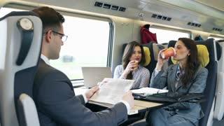 Happy businesswomen drinking coffee in train, steadycam shot