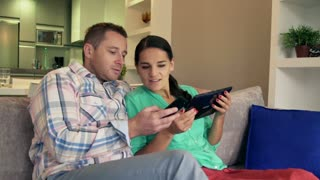 Happy couple sitting on the sofa and using modern technology, steadycam shot