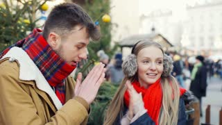 Happy couple standing at christmas square and looking very cold, steadycam shot
