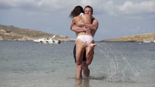 Happy couple swirling on the beach, slow motion shot at 240fps