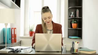 Happy, elegant businesswoman working on laptop in the office, steadycam shot