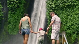Happy family looking on beautiful waterfall, slow motion shot at 240fps