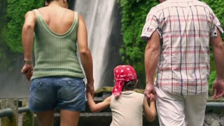 Happy family looking on beautiful waterfall, slow motion shot