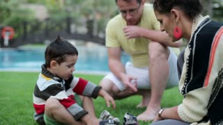 Happy family sitting by the swimming pool and talking, steadicam shot