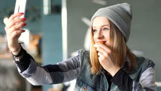 Happy girl doing selfie on smartphone while eating pizza