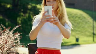 Happy girl doing selfies on smartphone while standing outdoors