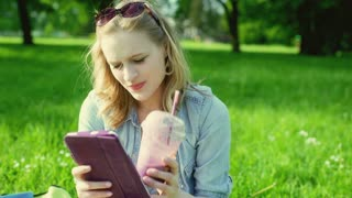 Happy girl drinking cocktail and using tablet in the park, steadycam shot