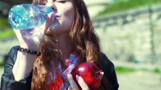 Happy girl drinking water from a bottle and holding red apple