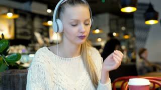 Happy girl finish listening music in the bistro and drinking coffee, steadycam s