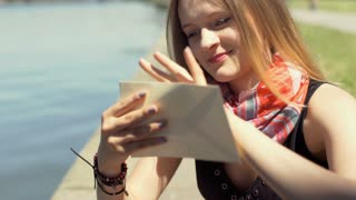 Happy girl holding envelope in her hands while sitting by the river