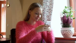 Happy girl in pink, fluffy sweater texting messages on smartphone