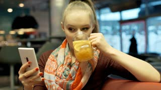 Happy girl in ponytail drinks delicious lemonade and types messages on phone