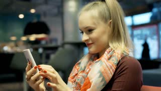 Happy girl in ponytail texting messages on smartphone in the cafe