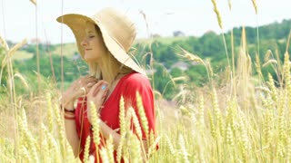 Happy girl in straw hat picking grain while standing on the field