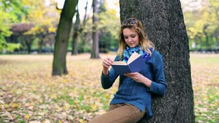 Happy girl leaning on tree and reading book in the park