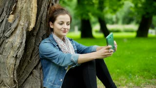 Happy girl leaning on tree in the park and doing selfies on smartphone