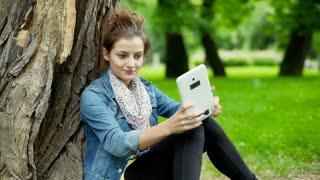 Happy girl leaning on tree in the park and doing selfies on tablet